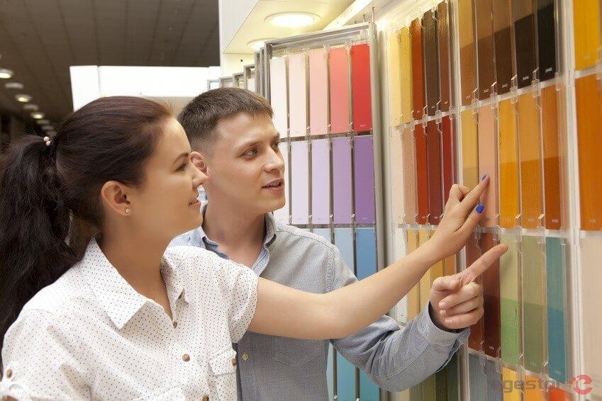 casal escolhendo cores em uma loja de tintas